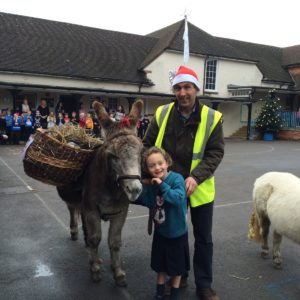 Harry the donkey, five-year-old Isla Rawlingson-Plant, her father Matthew, with Bruton Primary school pupils in the background.