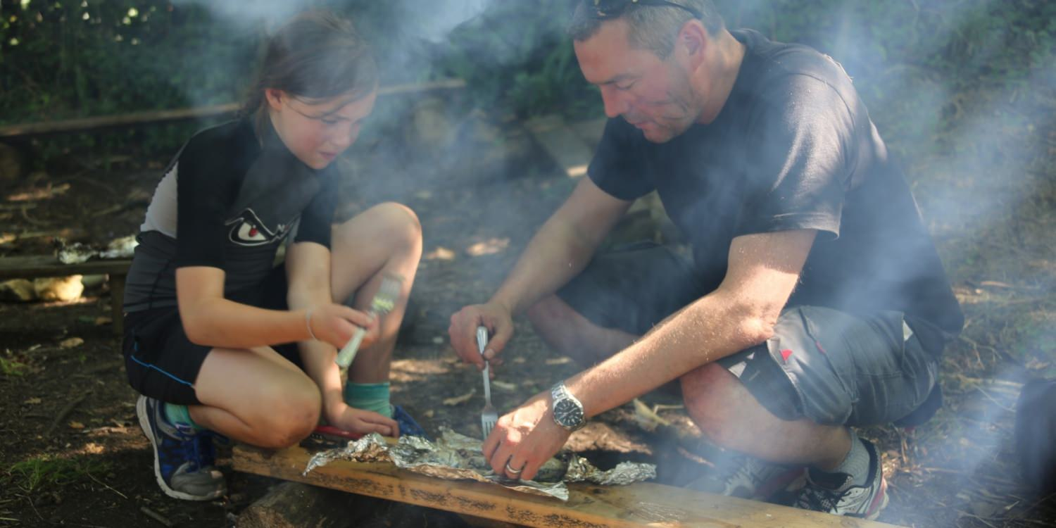 Father and daughter cooking outdoors